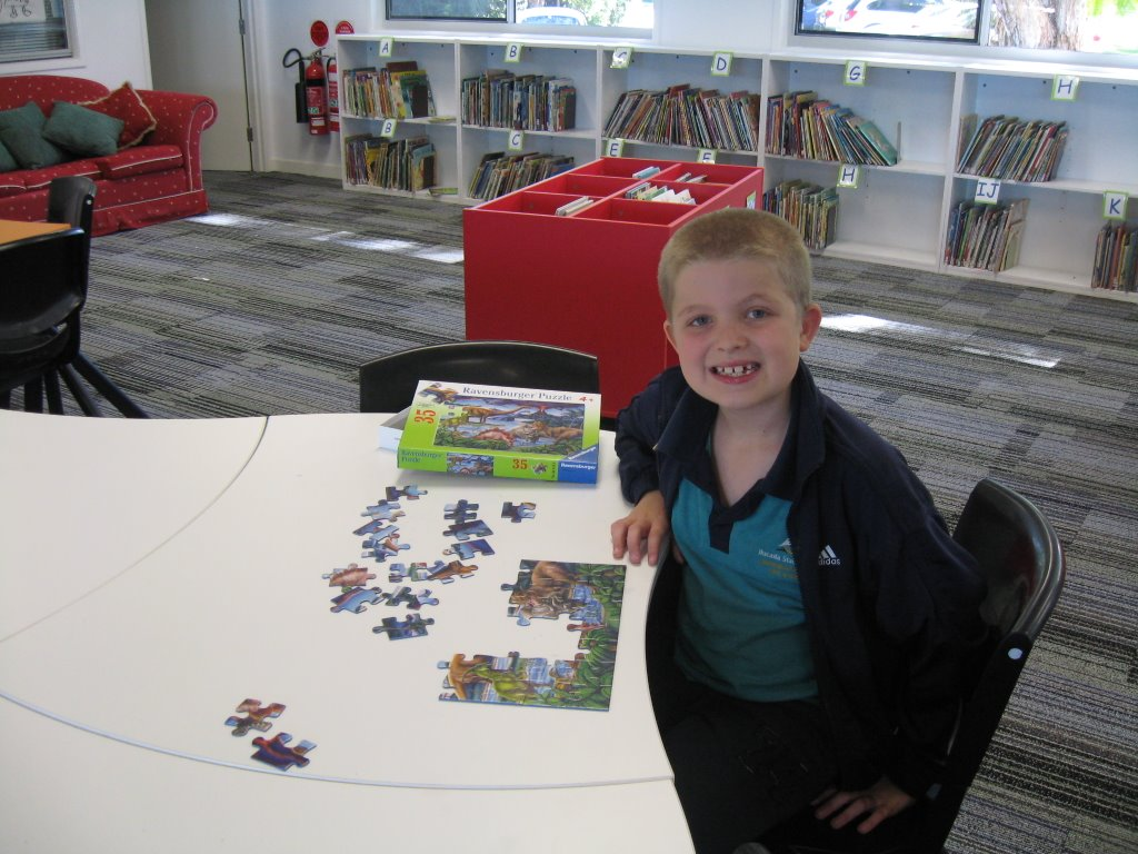 a school kid in library playing puzzle